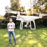 Young hipster man with flying drone. Sunny green nature.