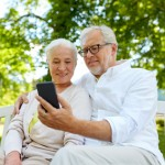 senior couple with smartphone taking selfie